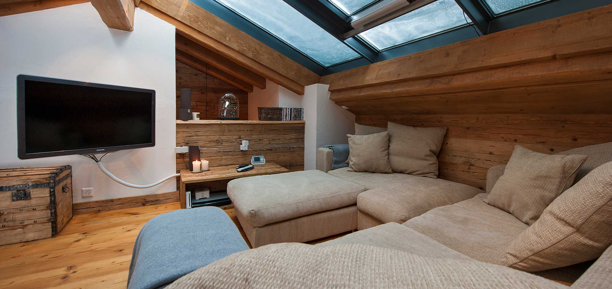 snowy roof windows above tv room sofa